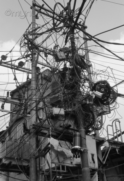 A messy telephone / electricity pole