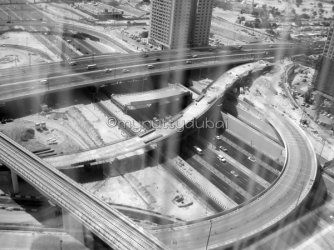 Through the window of a building - looking down onto the construction of the highways in Dubai
